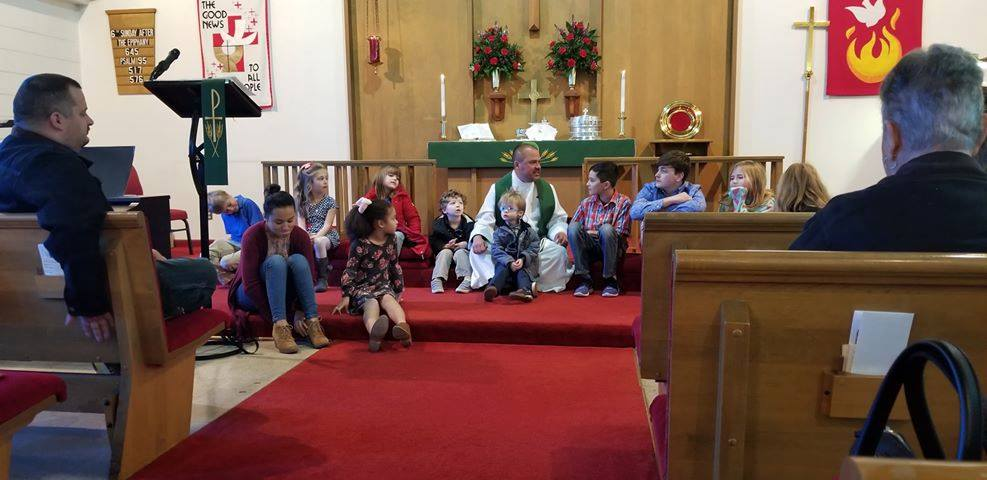 Pastor Christina sitting with children during the children's message.